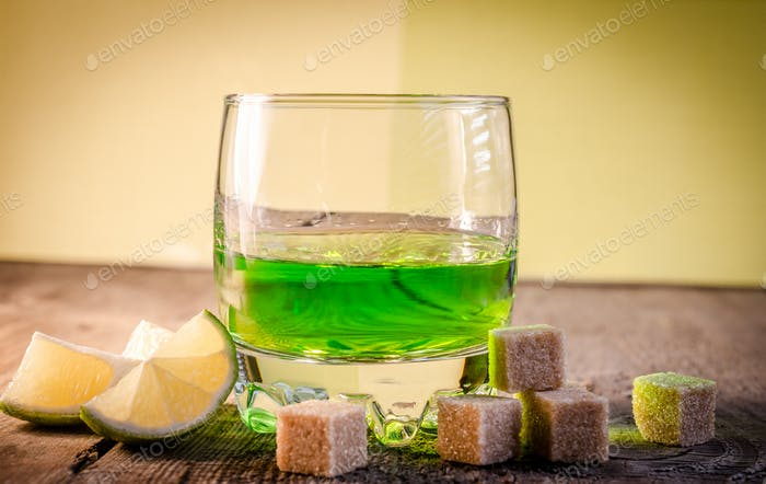 Glass of absinthe with lime and sugar cubes