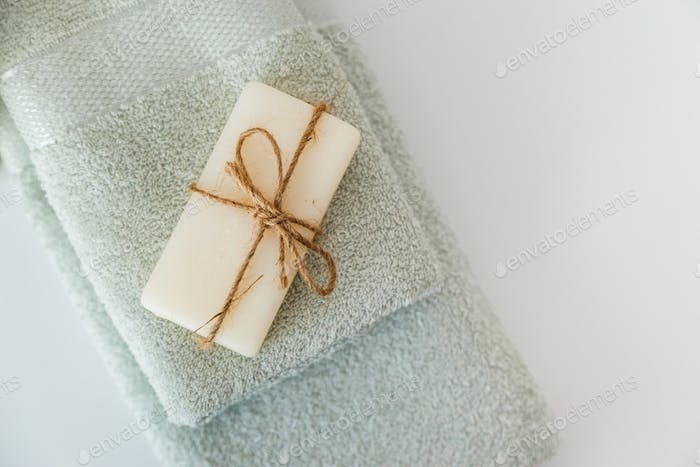 Solid soap corded on bath towels on white background with copy space. Top view with copy space