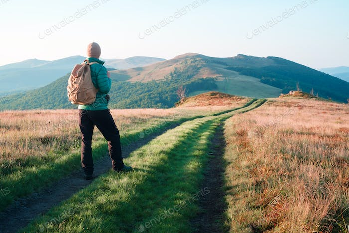 Man with backpack on mountains road