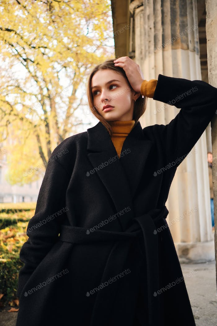 Beautiful serious girl confidently looking away posing on beautiful autumn city street