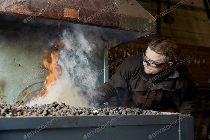 Ein handwerklicher Metallarbeiter, der Metall in einem Ofen Feuer heizt.