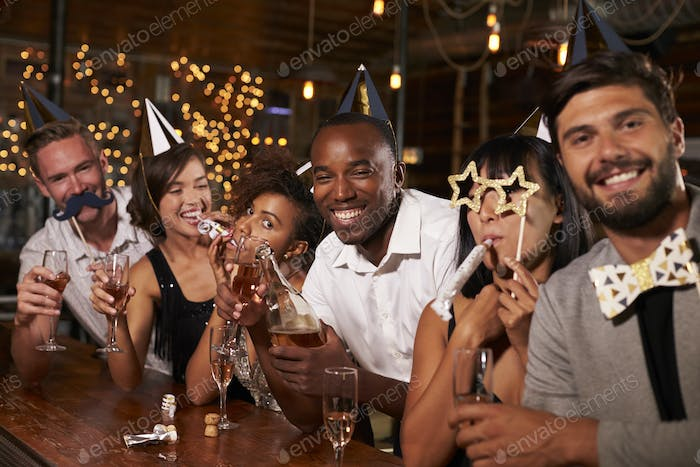 Friends celebrating New Year's Eve at a party in a bar