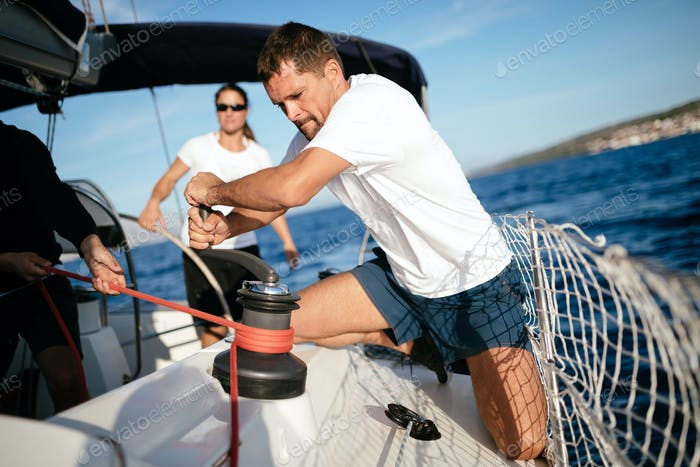 Handsome strong man sailing with his friends