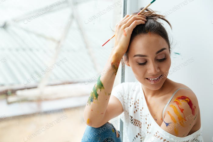Woman dirty with paints sitting and holding paintbrush