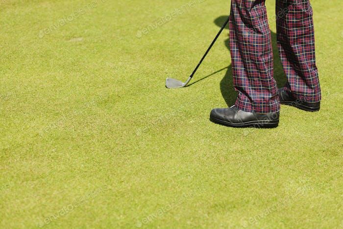 Низкая секция человека с гольф-клубом на поле