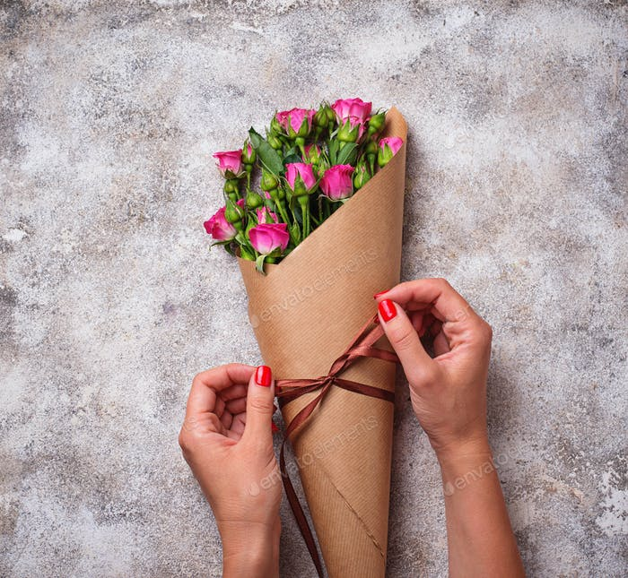 Womens hands wrap a bouquet of roses in paper