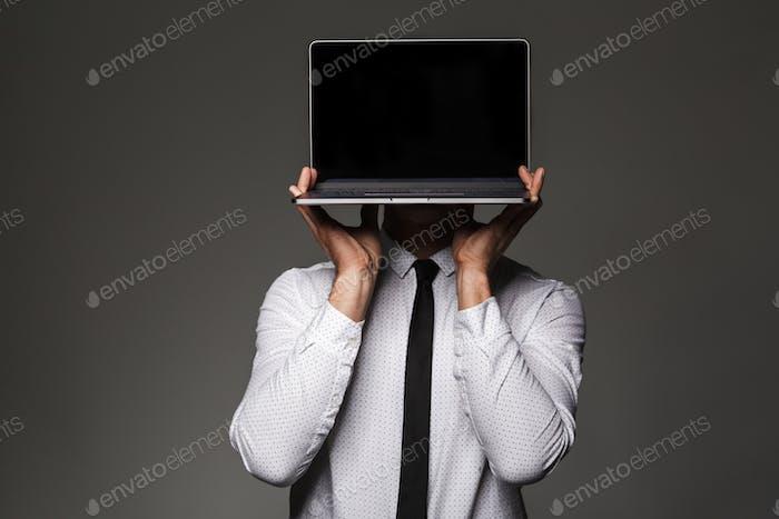 Portrait of caucasian male office worker posing on camera holdin
