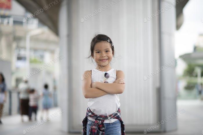 Smart little girl child standing in city