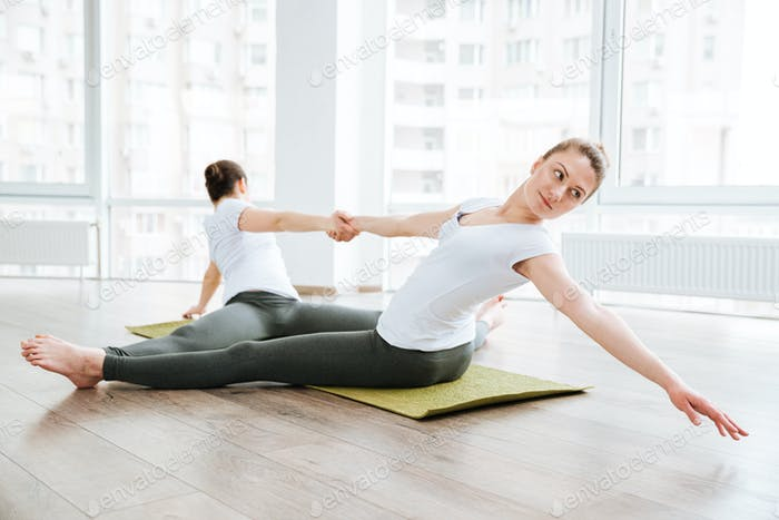 Two women stretching and relaxing in yoga center