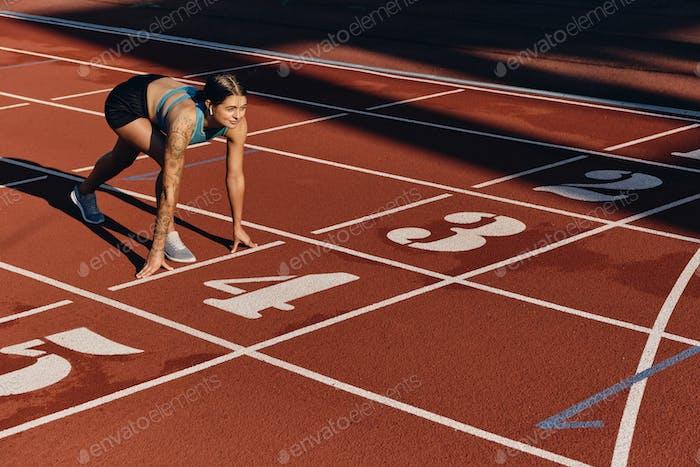 Attraktives Mädchen in Sportbekleidung stehend in Ausgangsposition bereit zum Laufen auf Stadtstadion
