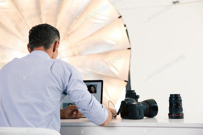 Back view portrait of photographer using laptop