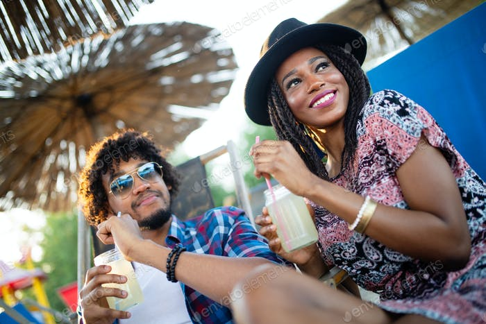 Happy black couple on the beach while relaxing on their deck chairs