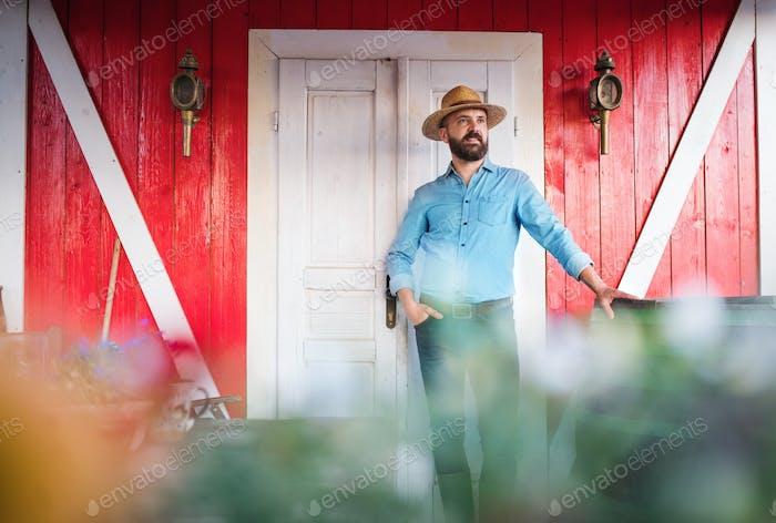 Ein Porträt von reifen Mann Bauer stehend im Freien vor der Familie Bauernhof