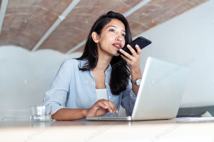 Elegant young business woman talking on mobile phone while working with her laptop in the office.