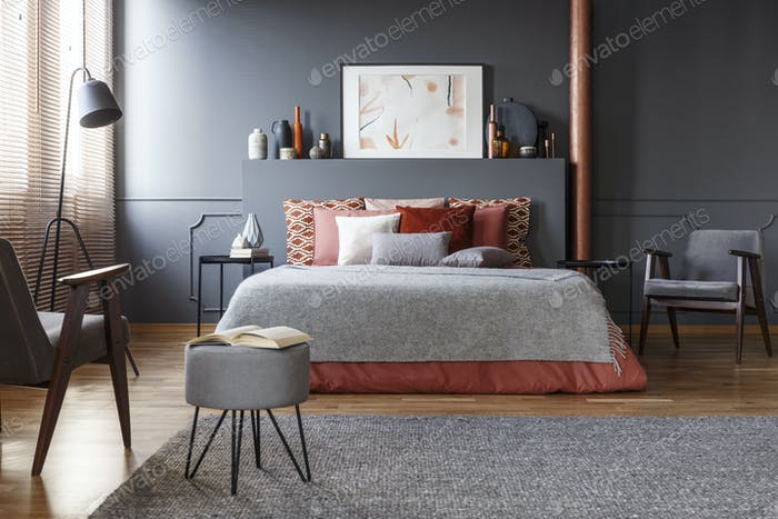 Real photo of cozy, dark bedroom interior with many decorative c
