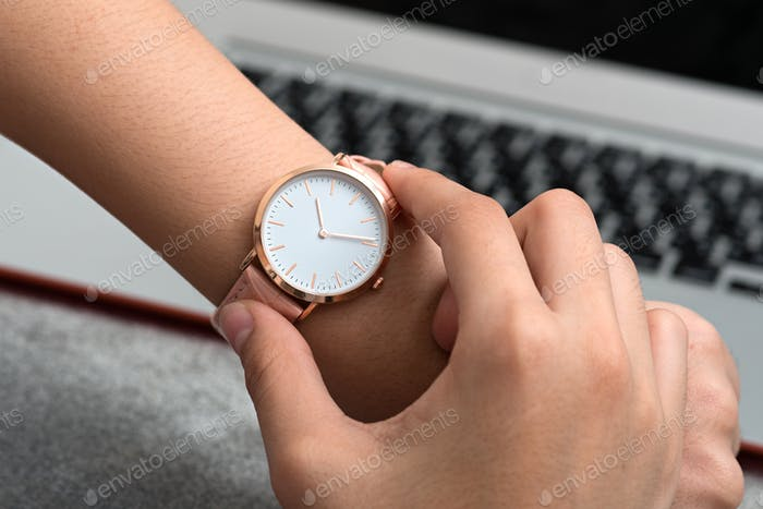 Wrist watch on girl's hand in front of a desk with notebook computer