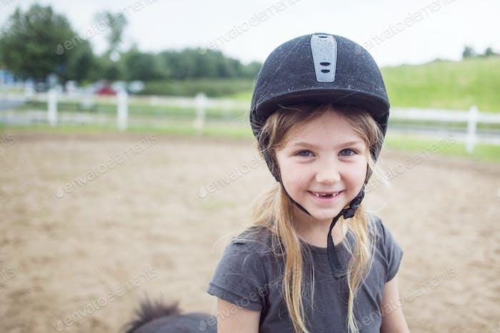 Portrait of girl (4-5) in equestrian helmet
