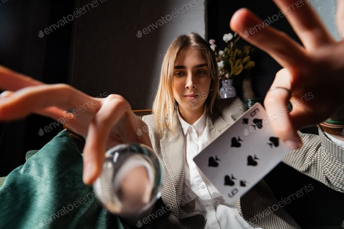 Woman in business suit holding crystal ball and six spade