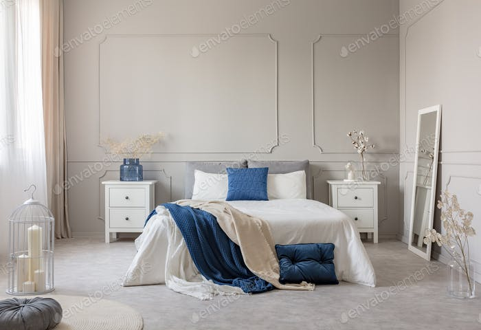 Blue pillow and blanket on white bed in spacious bedroom interior, copy space on empty grey wall