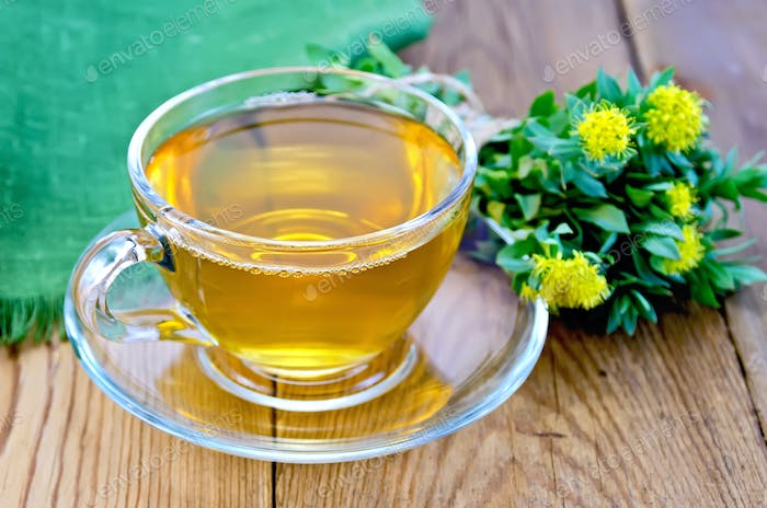 Herbal tea with a bouquet of Rhodiola rosea on the board