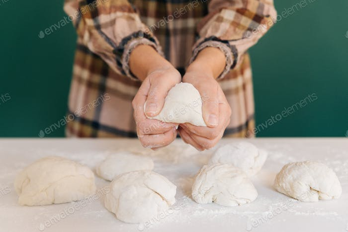 Woman prepares to her home handmade pieces of dough for bread, homemade cooking.