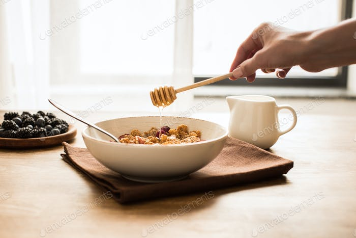 person pouring honey into corn flakes in bowl
