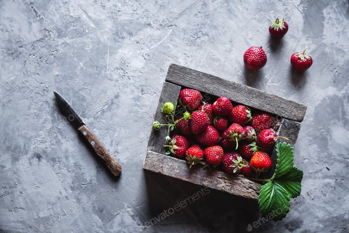 Fresh strawberries in an old box on a gray background. Healthy food, fruit