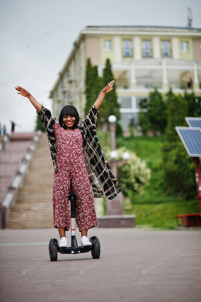 African american woman using segway or hoverboard