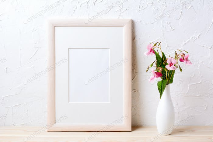 Wooden frame mockup with purple wildflowers in elegant vase