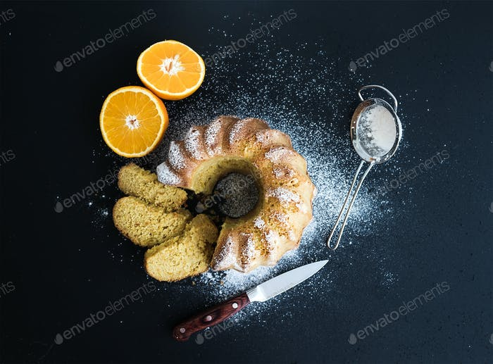 Moist orange bundt yoghurt cake with sugar powder on top, dark grunge background.