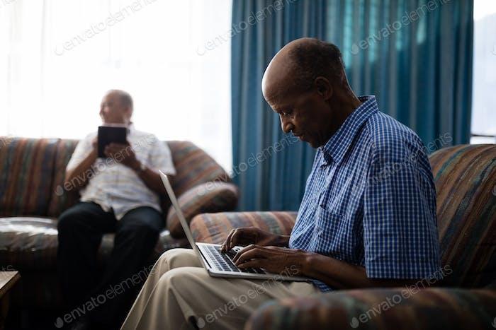 Senior man using laptop while sitting on sofa