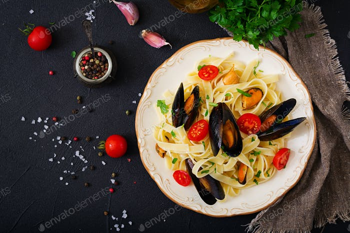 Seafood fettuccine pasta with mussels over black background