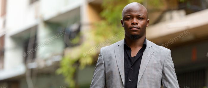 Young handsome bald African businessman in suit outdoors