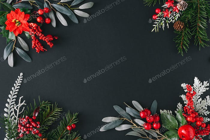 Christmas dark background made of natural winter things. Flat lay border frame with copy space.