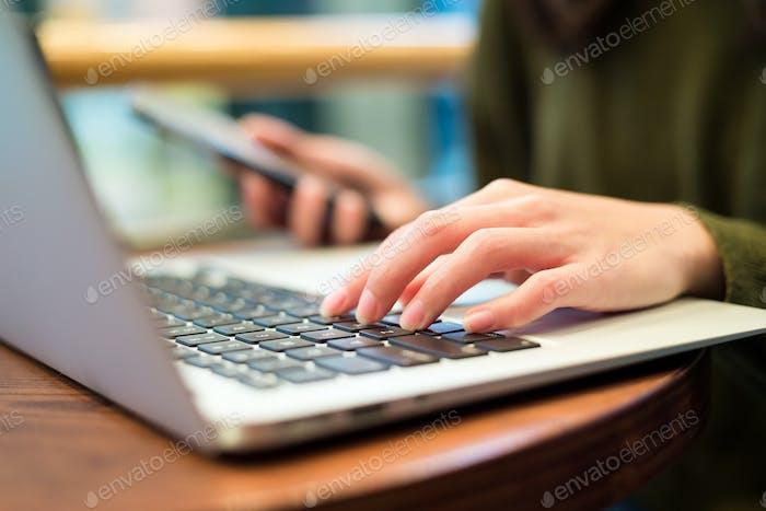 Frau arbeitet auf Laptop-Computer und Handy