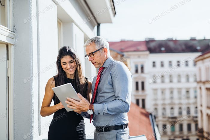 Man and woman business partners with tablet standing on a terrace in city, talking.