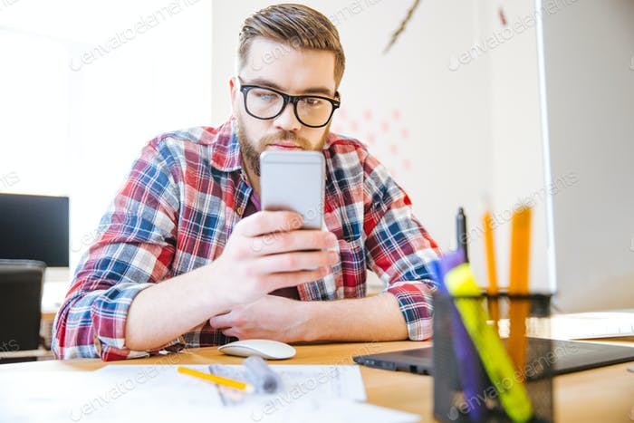 Handsome man sitting at the table and using cell phone