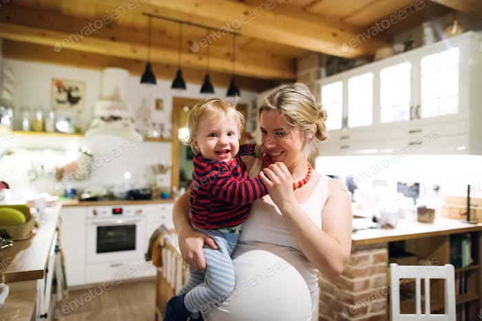 Beautiful Pregnant Woman Carrying A Toddler Boy In The Kitchen At Home