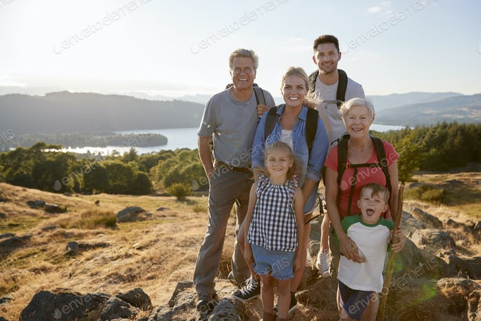 Portrait Of Multi Generation Family Standing At Top Of Hill On Hike Through Countryside