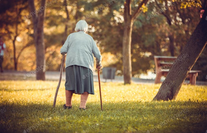 Senior woman with canes walking in autumn park