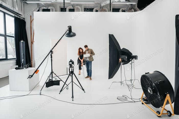 professional photographer and beautiful model with laptop in photo studio with lighting equipment