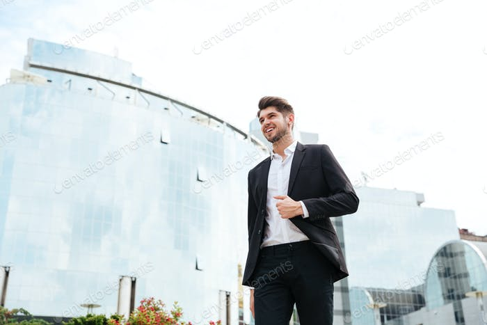 Cheerful young businessman walking outdoors