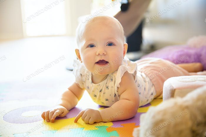 Happy baby girl with blue eyes playing on floor mate