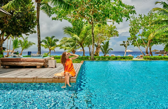 Woman by poolside. Resort swimming pool at Seychelles.