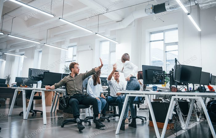 People talking and working together in the modern office near computers