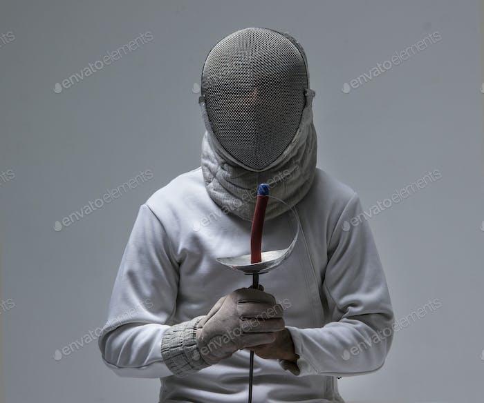 Retrato de un esgrimista en una máscara de esgrima con una espada sentado en la silla