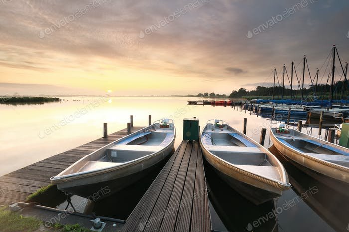 sunrise over boats on harbor over big lake