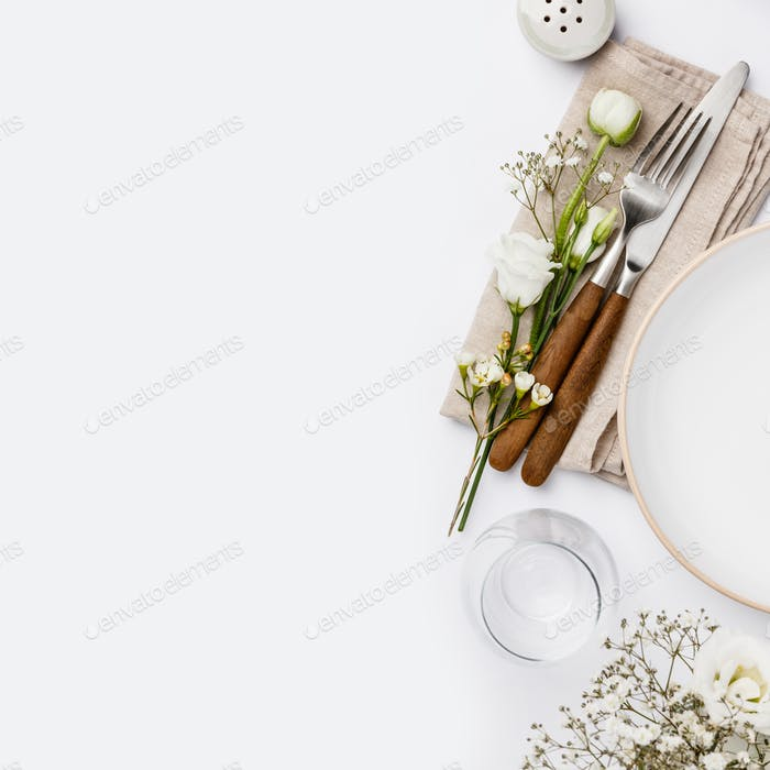 Empty white plate and cutlery on a napkin