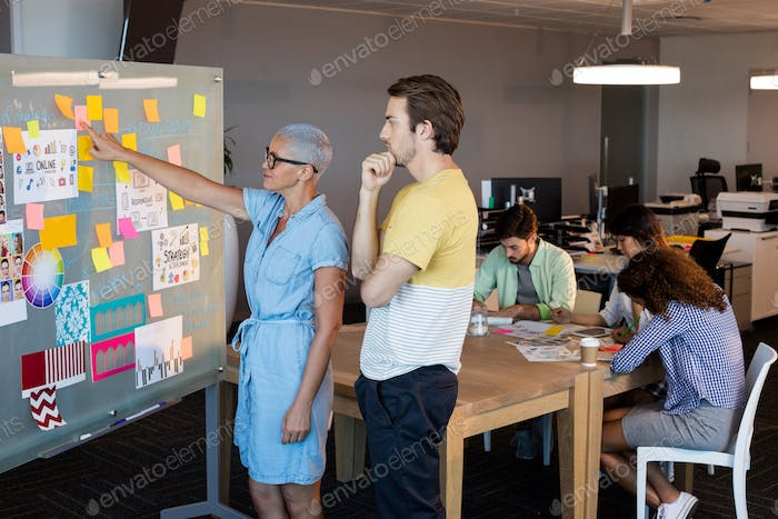 Creative business people looking at sticky notes on glass board