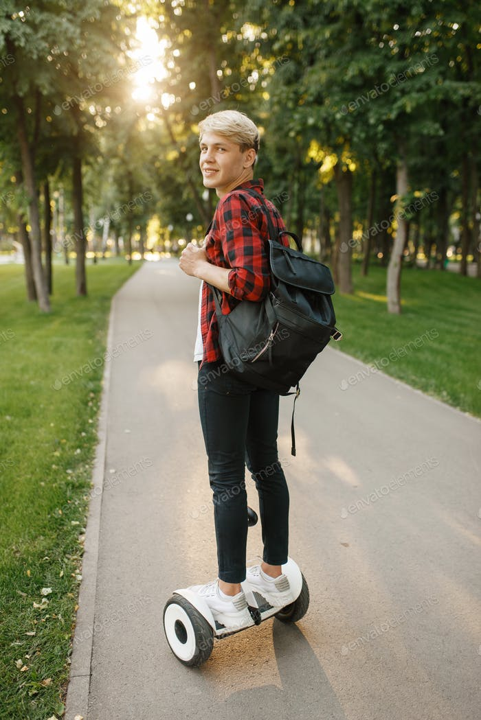 Young man with backpack riding on mini gyro board